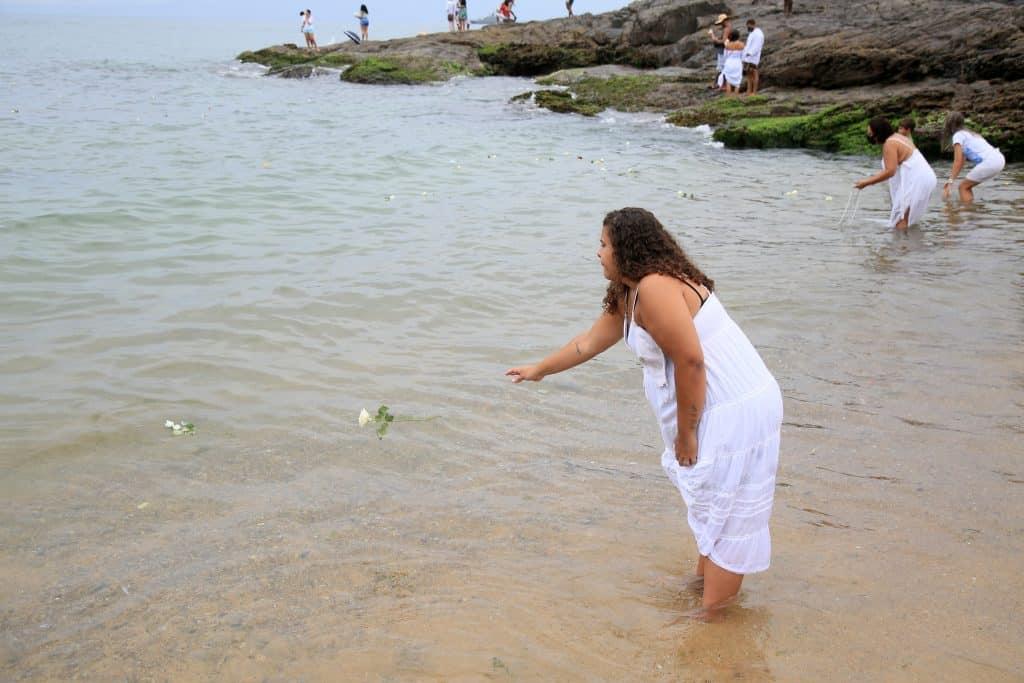 Imagem do mar e várias pessoas, homens e mulheres integrantes do Candomblé, na água se preparando para o banho de Iemanjá.