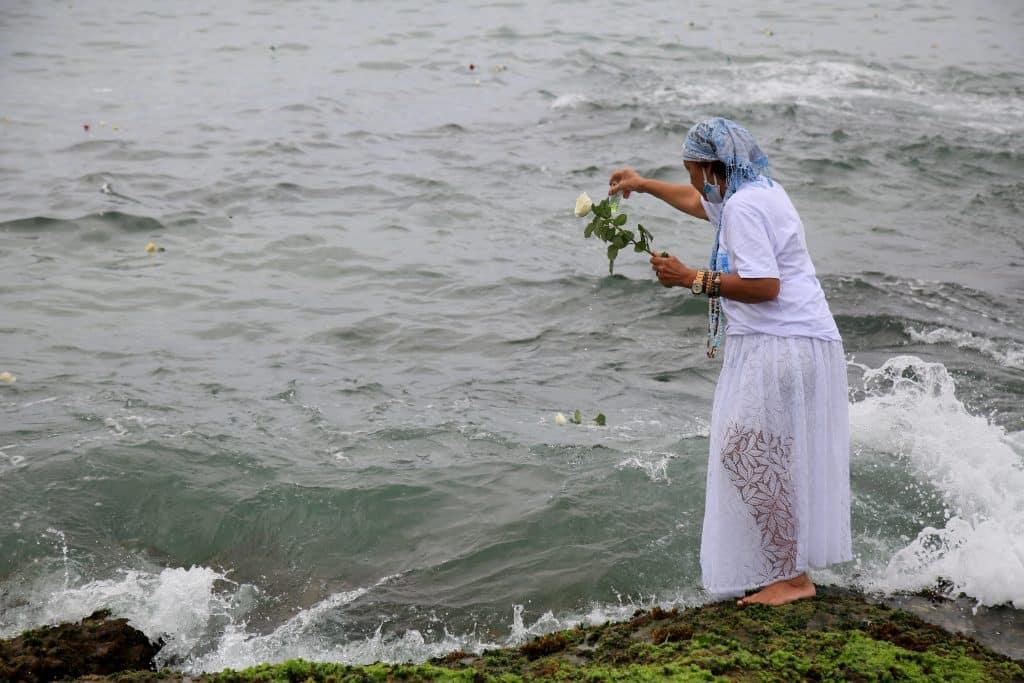 Imagem do mar e de uma mãe de santo jogando pétalas de rosas-brancas na água preparando o banho de Iemanjá.