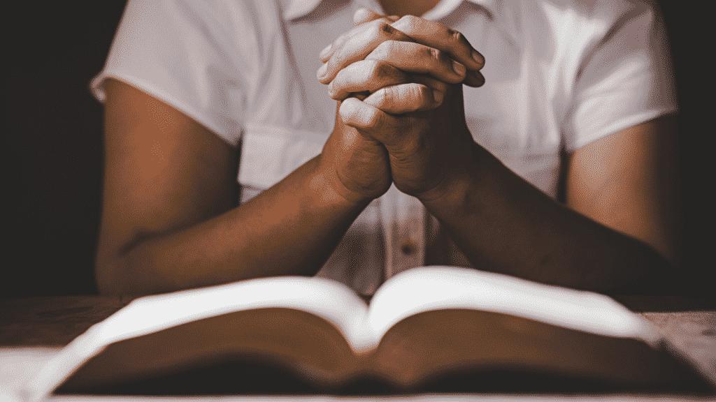 Pessoa orando com a bíblia no colo