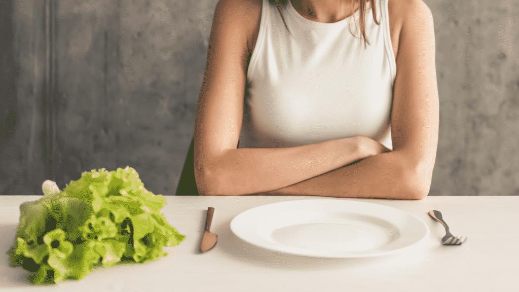 Garota de dieta com prato vazio e um pé de alface ao lado