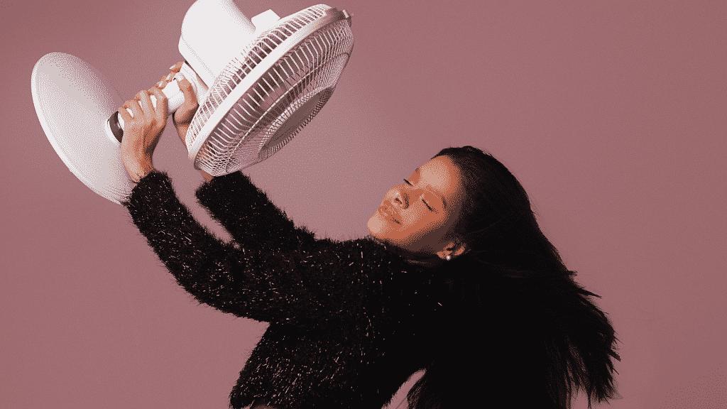 Mulher segurando ventilador se refrescando