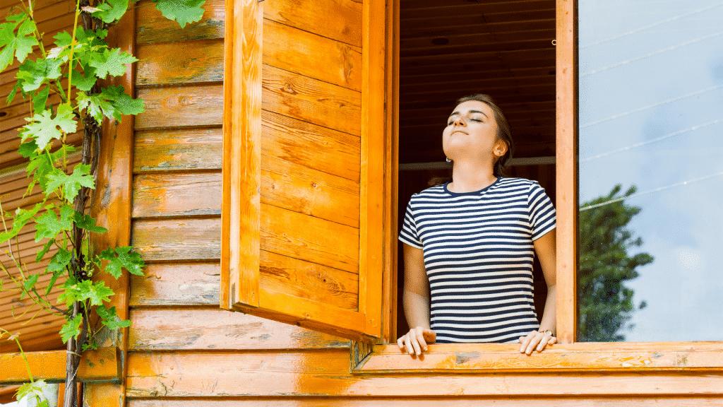 Garota na janela respirando fundo