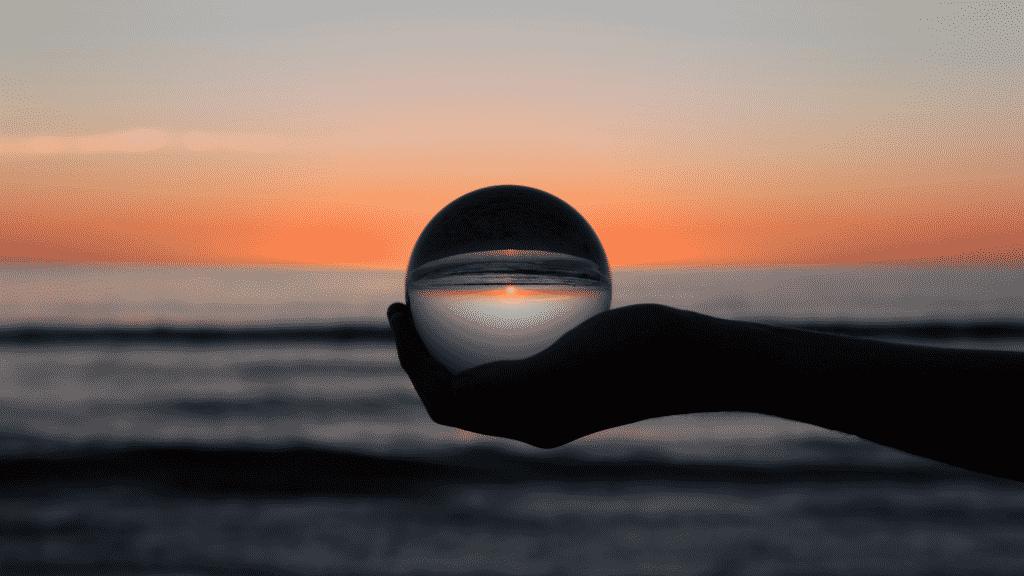 Foto de uma bola de cristal representando o mundo espelhando o por do sol