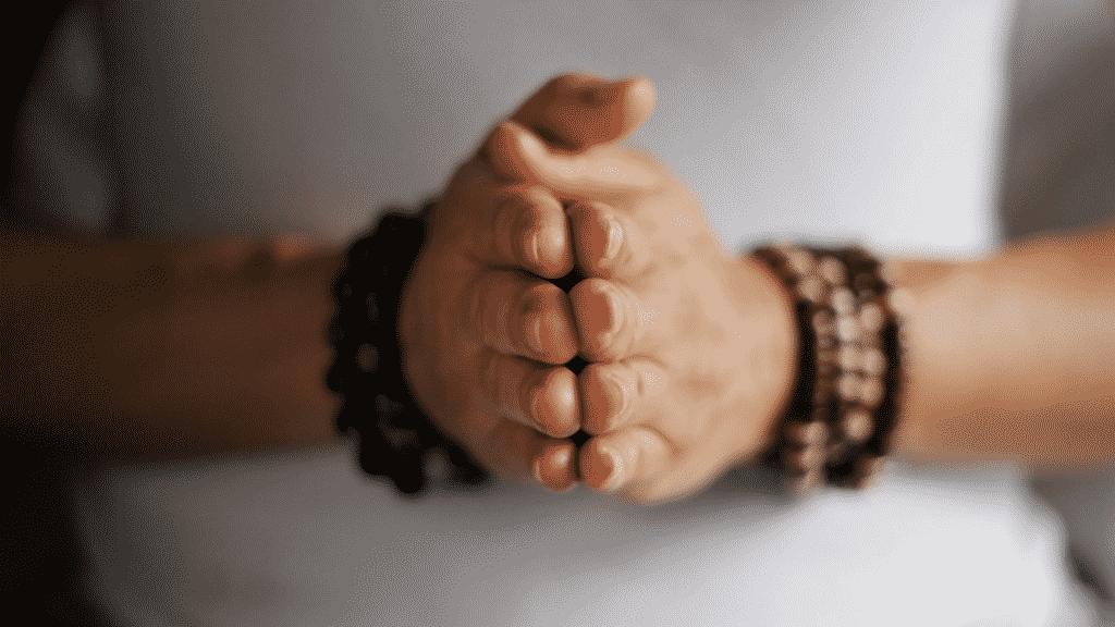 Mãos juntas em pose de yoga