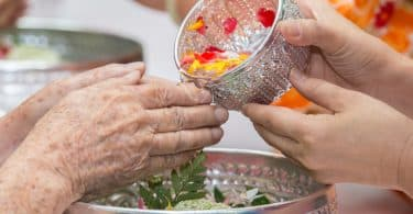Imagem de um benzimento nas mãos de uma senhora. A benzedeira está lavando as mãos dela com água aromatizada que está dentro de um pote prateado.