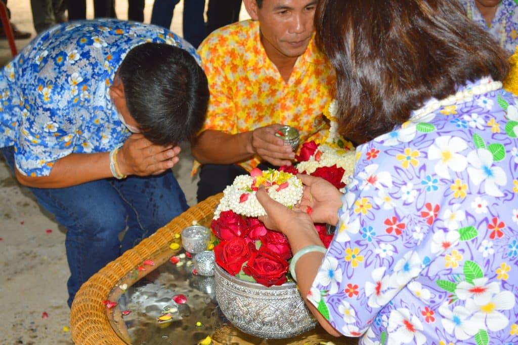Imagem de dois homens sendo benzidos por uma senhora em um ritual onde ela coloca várias flores e água.