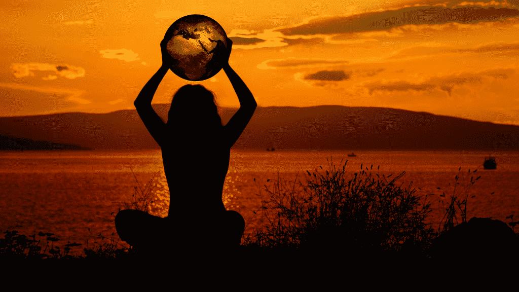 Mulher meditando segurando uma representação do globo enquanto observa o por do sol