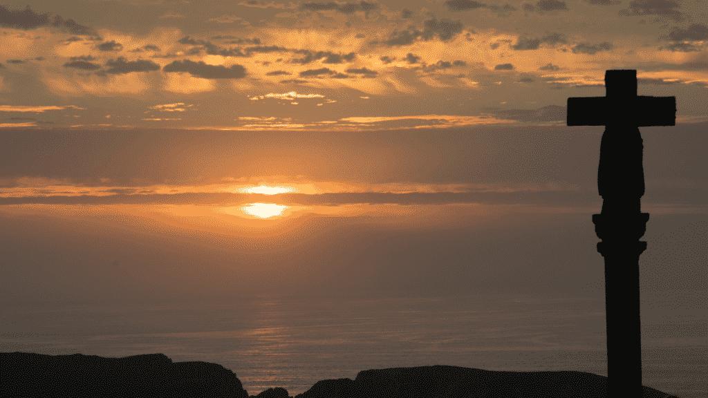 Silhueta de uma cruz em meio o pôr do sol