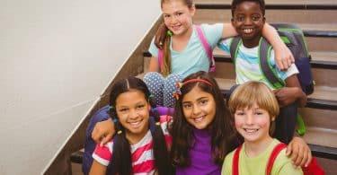 Retrato de alunos sentados na escada da escola.
