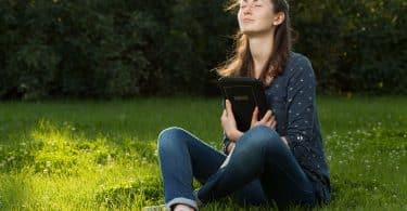 Mulher sentada sobre grama. Ela está segurando uma bíblia.