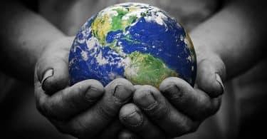 Homem segurando um globo terrestre nas mãos.