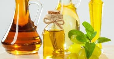 Imagem de quatro garrafas diferentes contendo óleo de semente de uva. Ao lado de uma delas um cacho de uvas verdes.