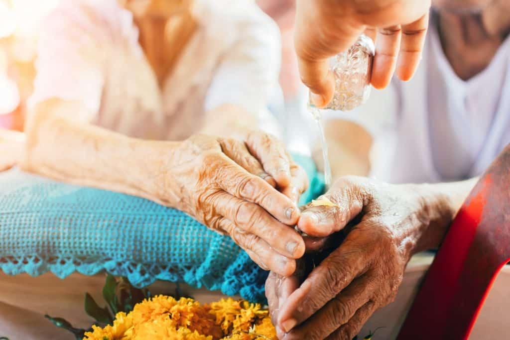 Imagem das mãos de um casal de idosos recebendo o benzimento com água. As mãos dela está disposta sobre uma almofada de crochê azul.