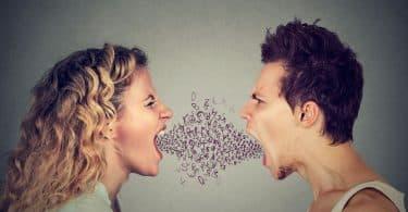 Homem e mulher, um em frente ao outro, gritam.