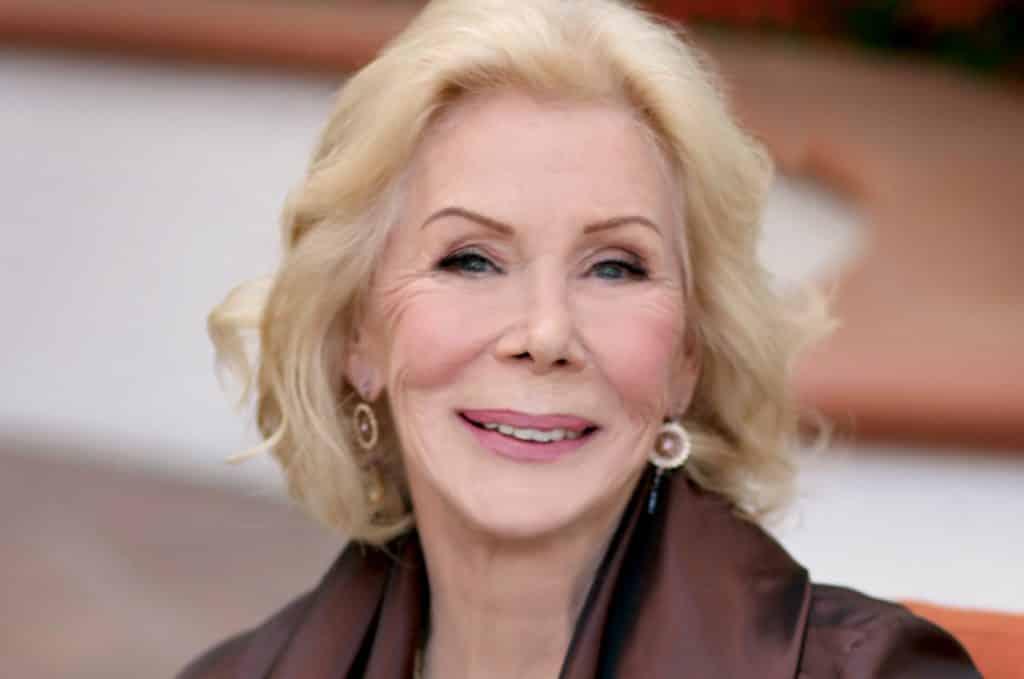 Mulher branca idosa de cabelos curtos e loiros, com expressão sorridente.