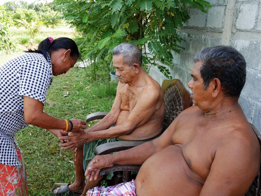 Imagem de uma senhora benzedeira fazendo um benzimento em dois senhores sentados.