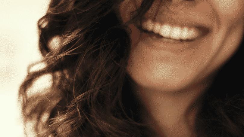 Foto com foco no sorriso de uma mulher