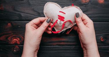 Pessoa costurando coração de pano
