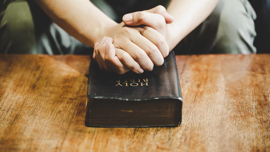 Pessoa com as mãos unidas sobre a bíblia