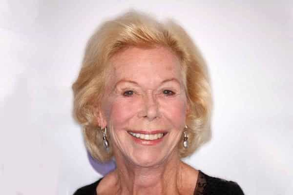 Mulher branca idosa de cabelos curtos e loiros com expressão sorridente.