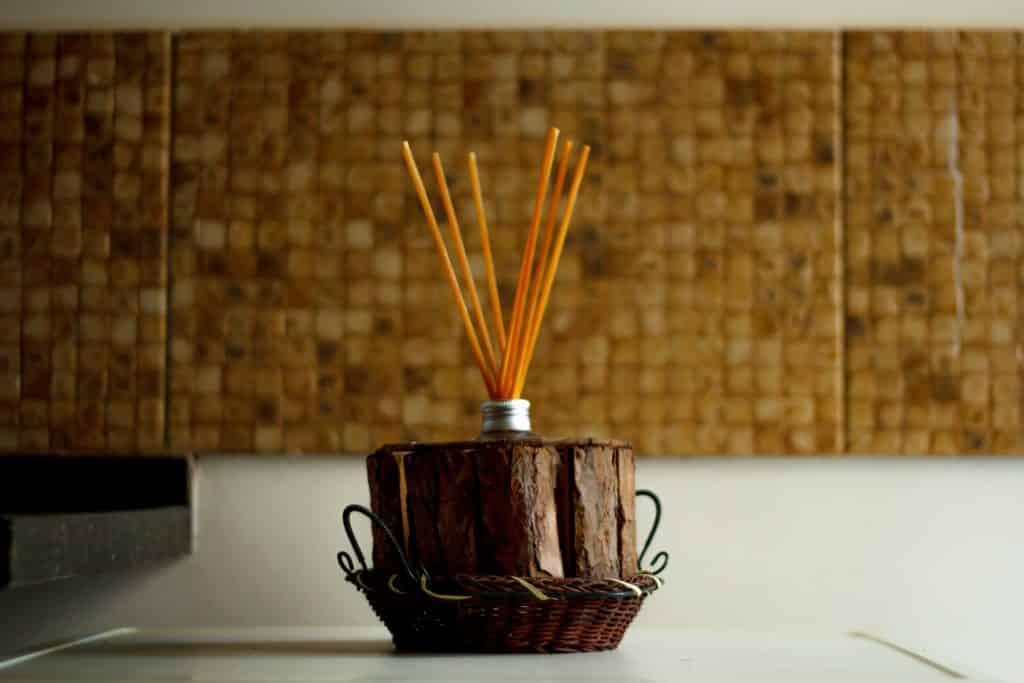 Imagem de vários palitos de incensos dispostos em um grande incensário de madeira colocado sobre uma mesa de fundo branco.
