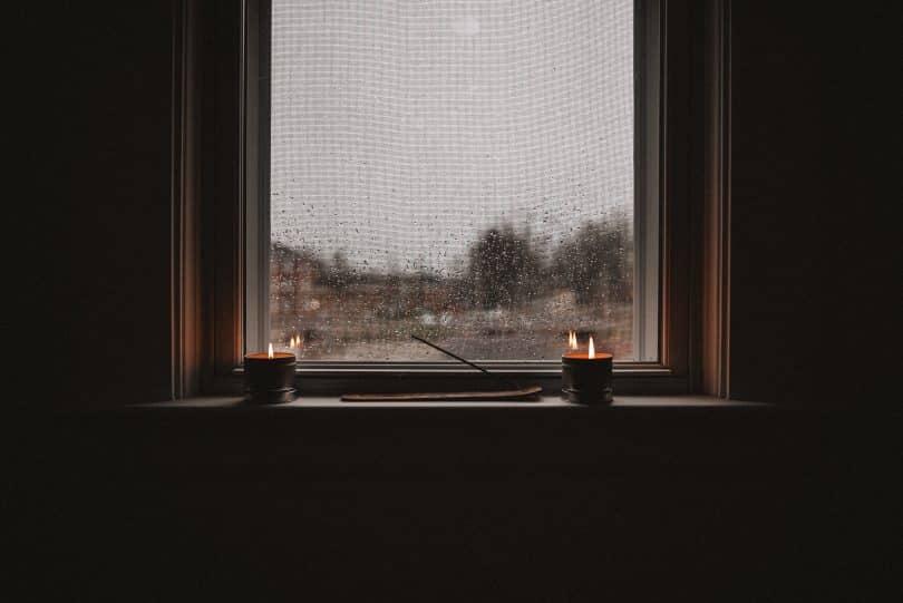 Imagem de uma janela sem cortina e um parapeito. Nesse parapeito interno dois vasos com velas acesas e um incenso de ananda no incensário sendo queimado.