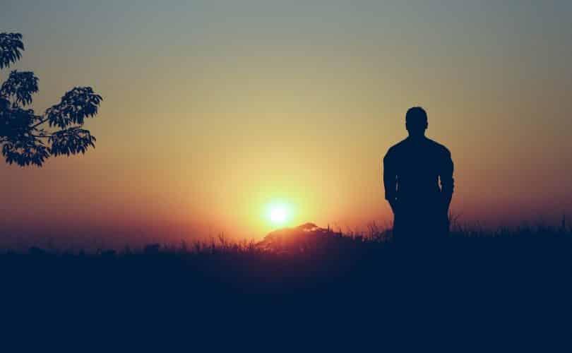 Imagem de fundo de um lindo pôr do sol e em destaque a silhueta de um homem sozinho. Ele está pensativo e se sentindo culpado por ter feito algo.