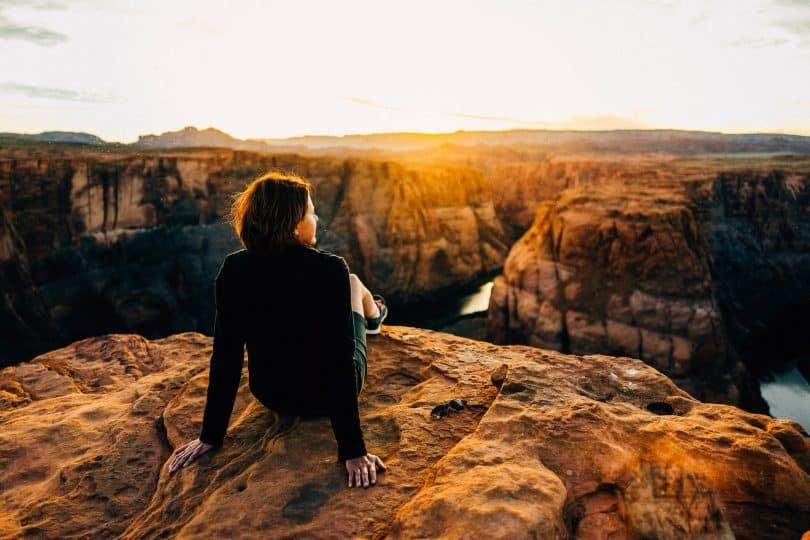 Mulher branca sentada de costas numa paisagem.