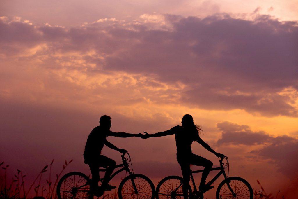 Imagem de um lindo pôr do sol e em destaque um casal sobre suas bicicletas um dando a mão para o outro.