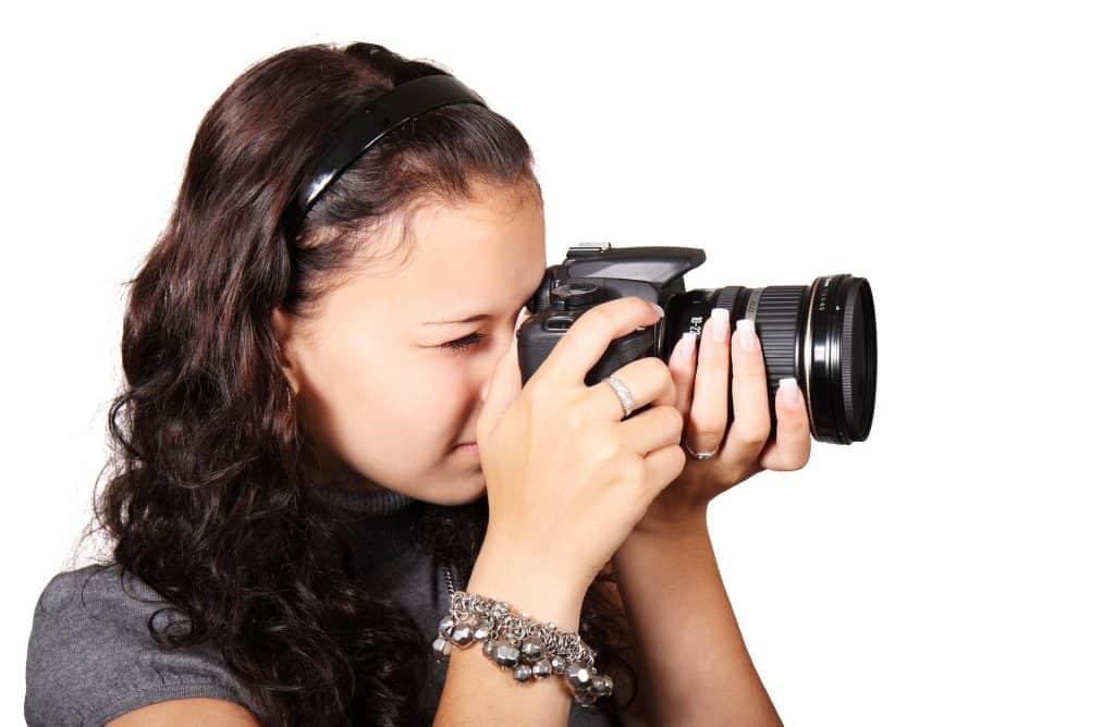 Imagem de uma linda mulher de cabelos longos e cacheados segurando uma câmera fotográfica digital em suas mãos e pronta para fotografar.