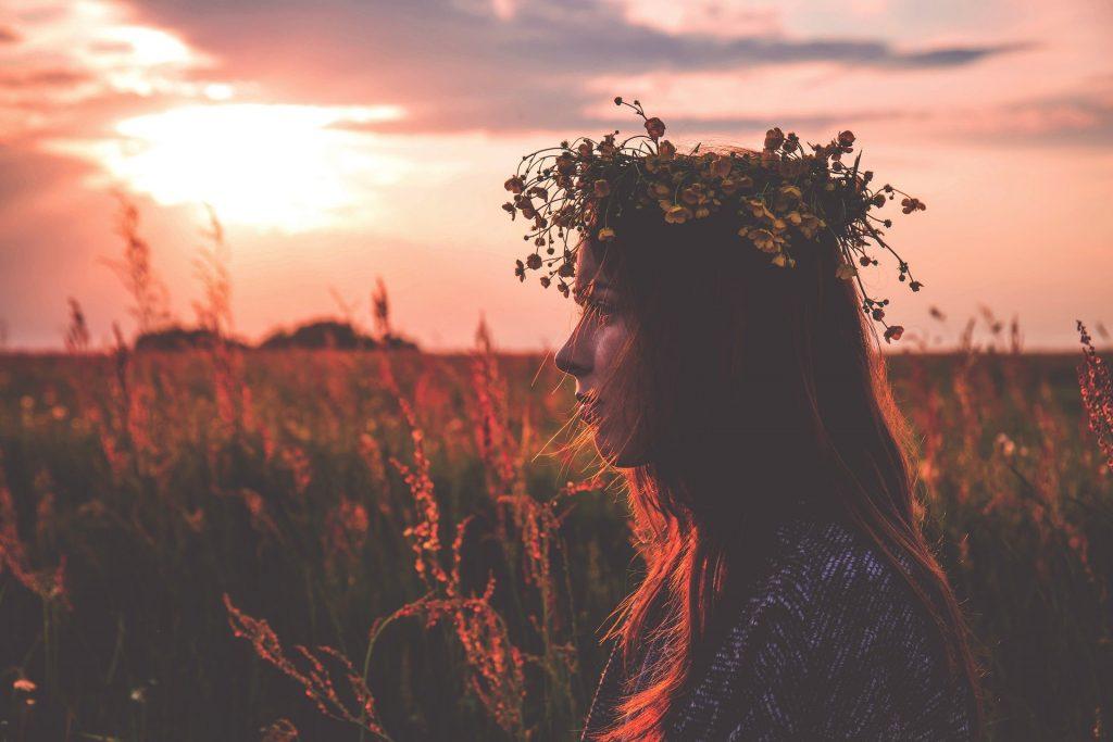Imagem de fundo de um lindo pôr do sol e em destaque uma jovem mulher de cabelos ruivos e longos decorados com uma coroa de flores nas cores amarela e laranja.