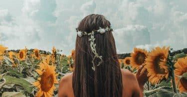 Mulher branca de costas num campo de girassóis.