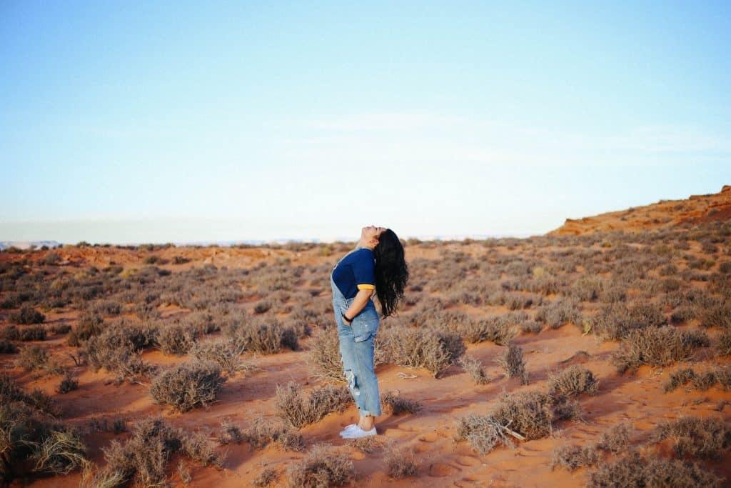 Mulher branca olhando para cima num deserto.