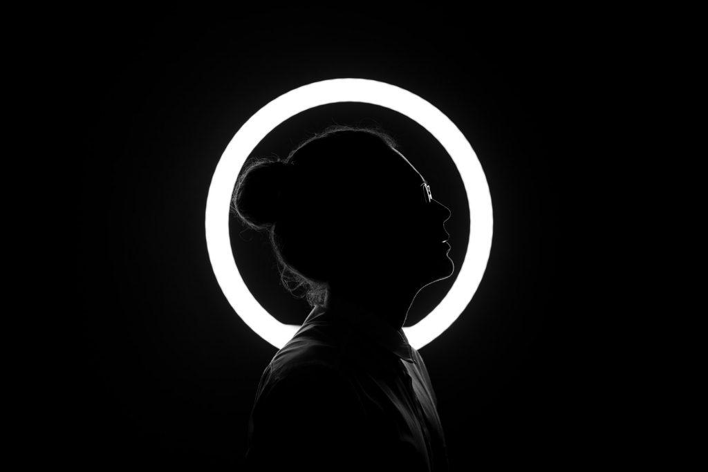 Silhueta de pessoa com circunferência de luz atrás.
