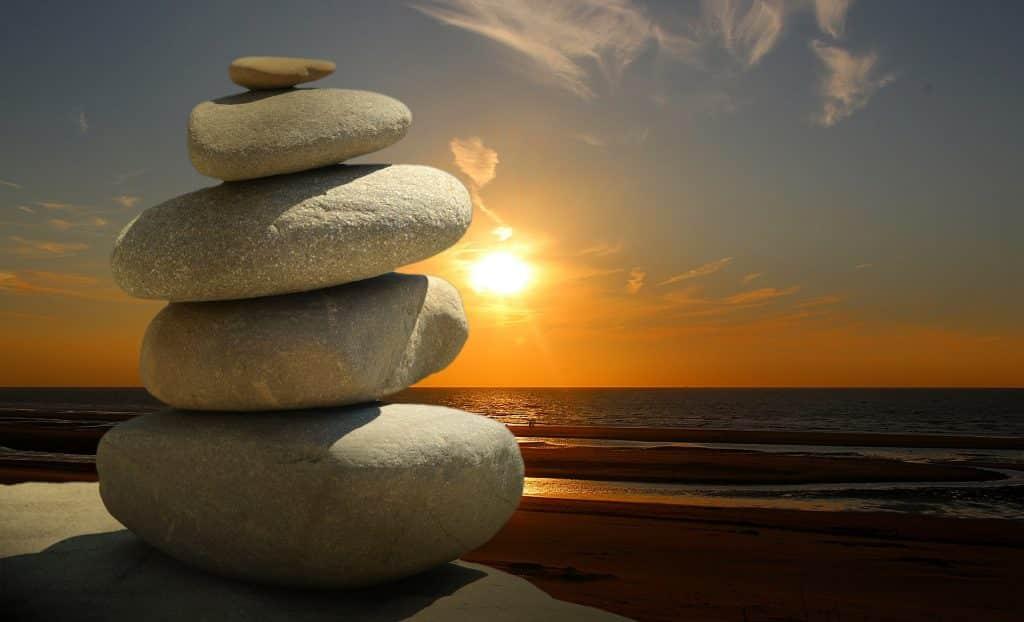 Imagem de fundo do pôr do sol em uma praia e em destaque várias pedras de diversos tamanhos empilhadas uma sobre a outra, representando o feng shui.