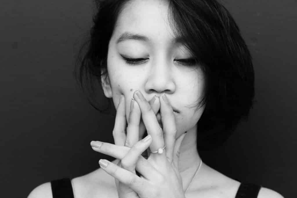 Mulher asiática de olhos fechados e mãos na boca come expressão irritada.