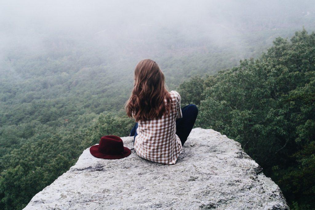 Imagem de uma jovem sentada em uma pedra. Ela usa camisa xadrez nas cores vermelho e branco, calças jeans escura e ao lado dela um chapéu na cor vermelha. Ao fundo uma grande mata encoberta com muitas árvores.
