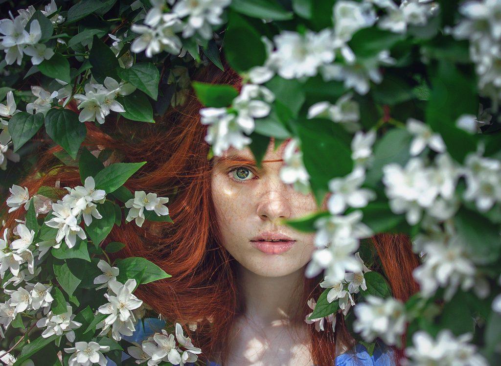 Imagem do rosto de uma linda mulher de cabelos ruivos entre uma folhagem com flores brancas. Ela representa uma fada, um ser puramente espiritual, encontrada na região superior da quarta dimensão espiritual.