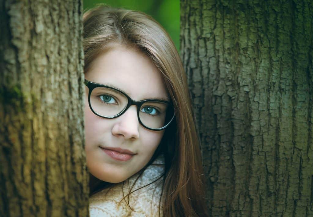 Imagem do rosto de uma jovem entre duas árvores. Ela usa o cabelo solto e um óculos de grau.