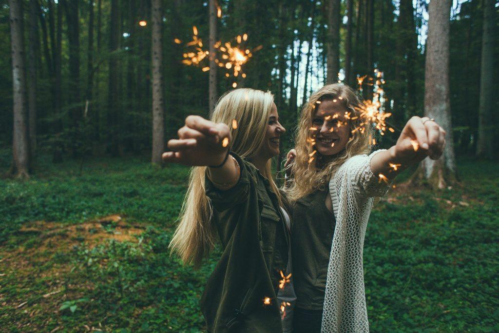 Imagem de duas amigas em uma floresta. Elas estão sorrindo e felizes. Ambas são loiras, com cabelos longos e cada uma segura em suas mãos uma vela que solta faíscas. Elas estão com blusas de frio - uma usa jaqueta na cor verde e a outra um cardigan de linha na cor bege.