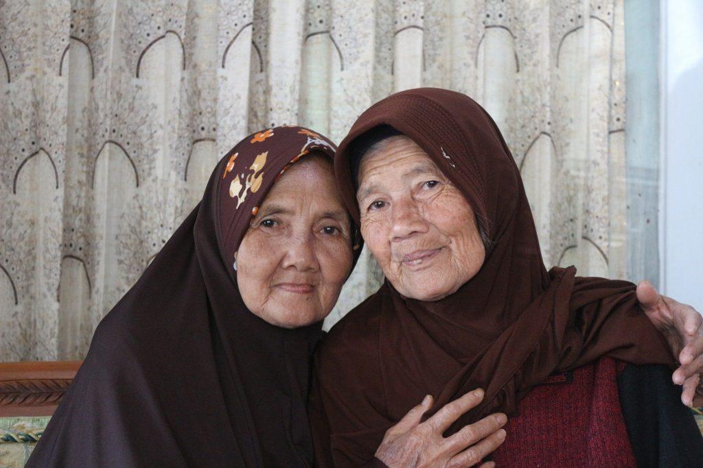 Imagem de duas senhoras sentadas usando lenços sobre suas cabeças. Ambas estão abraças e sendo generosas uma com a outra.