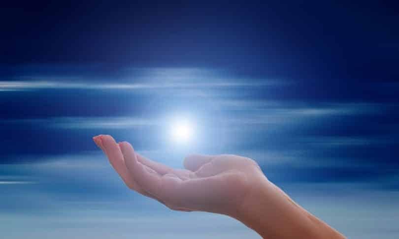 Imagem de fundo azul com o sol. Em destaque uma mão estendida, parecendo que está segurando o sol que relfete muita luz.