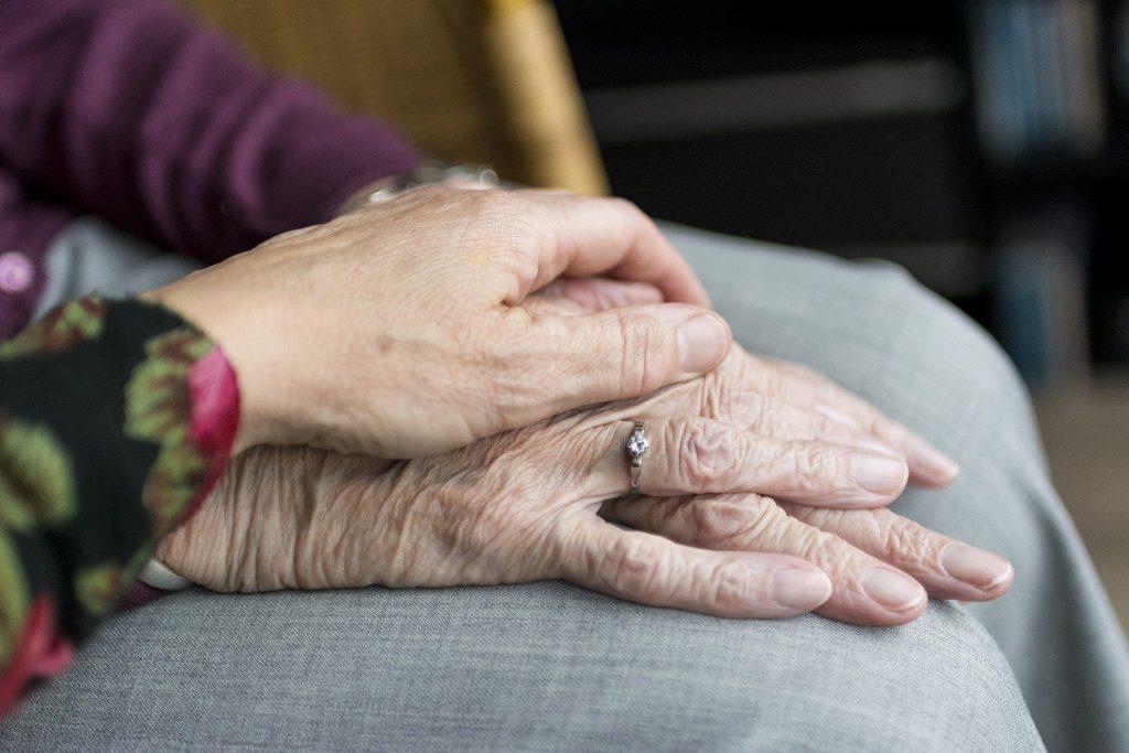 Imagem de uma pessoa idosa sentada com as mãos sobre as pernas. Sobre as mãos da idosa as mãos de uma pessoa mais jovem, segurando as mãos dela.
