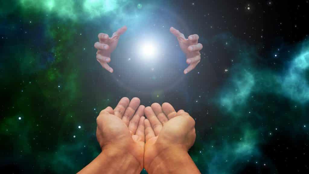 Imagem de fundo do universo e em destaque as mãos recebendo a energia que vem do sol e do próprio universo.