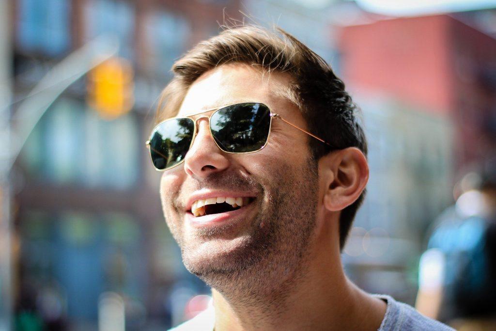 Imagem do rosto de um homem. Ele usa óculos de sol e está muito alegre e sorrindo.