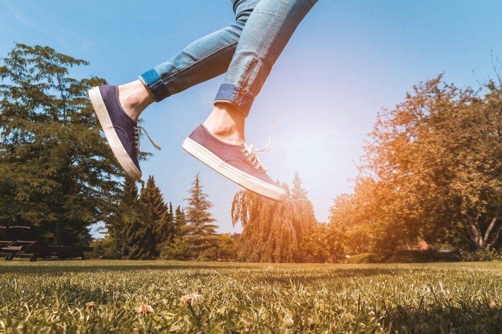 Imagem das pernas de um jovem fora do chão. Ele está saltando em um lindo gramado. Ao fundo um lindo pôr do sol.