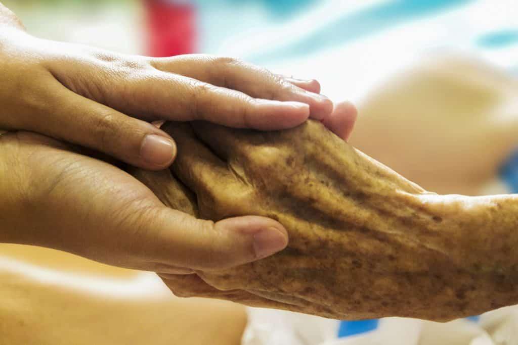 Imagem de uma mão idosa sendo segurada por uma mão de uma pessoa jovem.