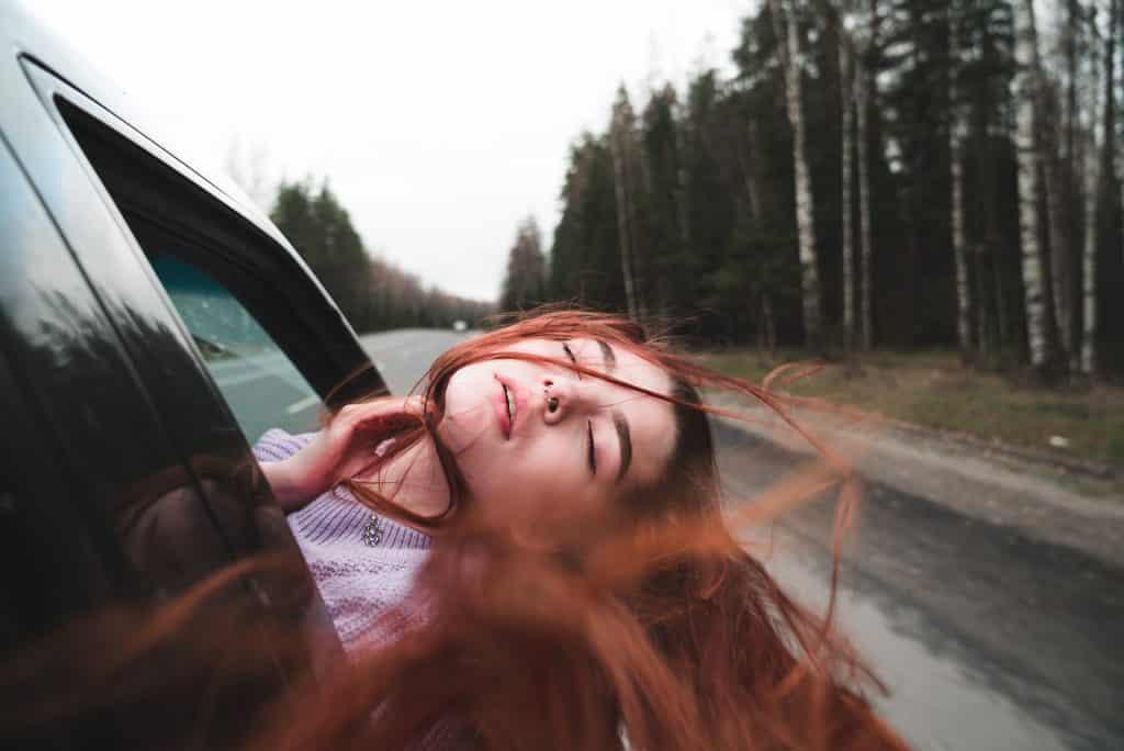 Mulher branca de cabelos ruivos com a cabeça para fora da janela de carro.