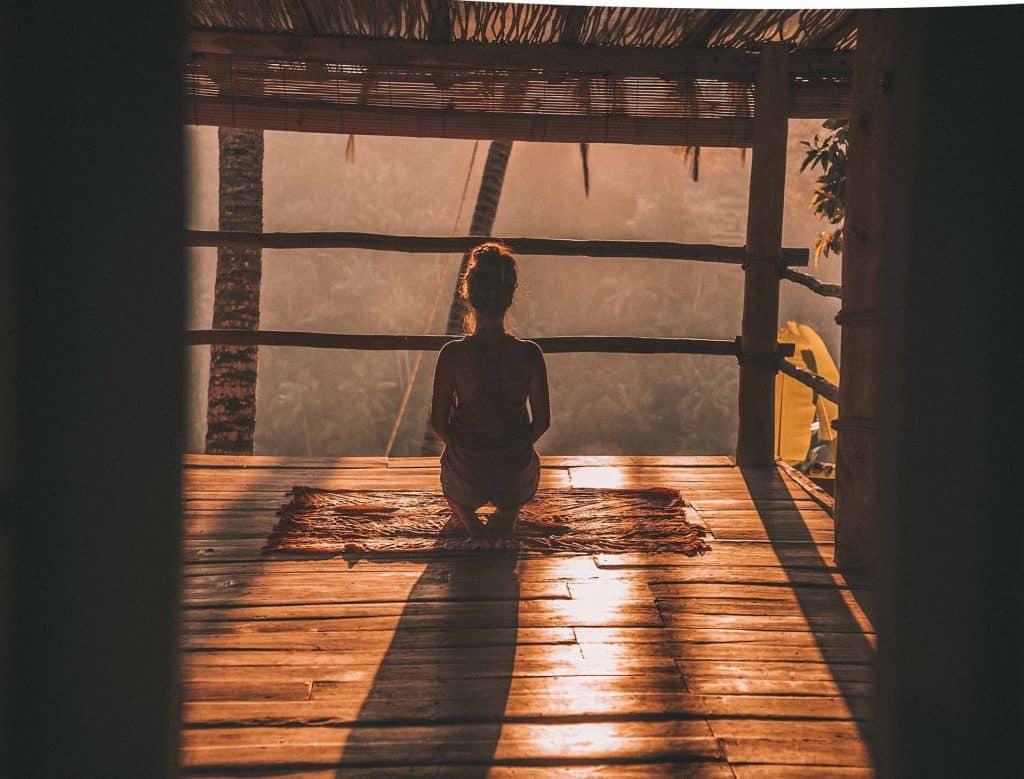 Silhueta de mulher de costas e agachada numa varanda de madeira.