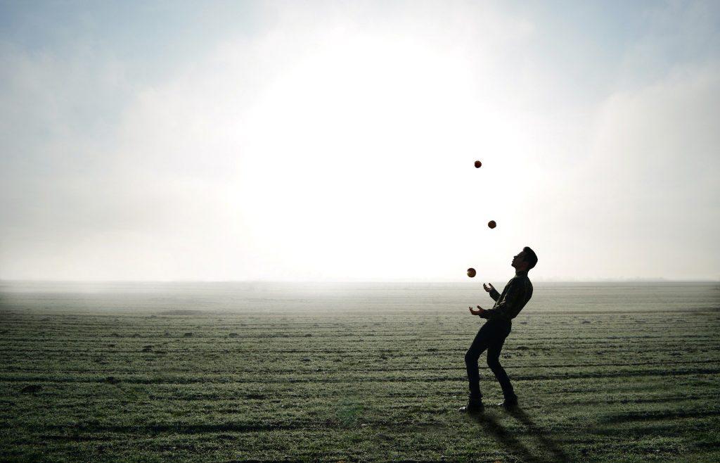 Imagem de um homem equilibrando três bolas. Ele joga ao alto as três bolas e faz o equilíbrio delas com as duas mãos.